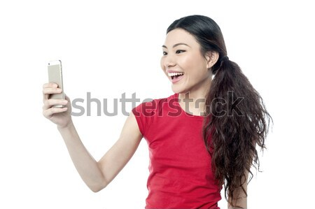 Amused girl clicking a selfie Stock photo © stockyimages