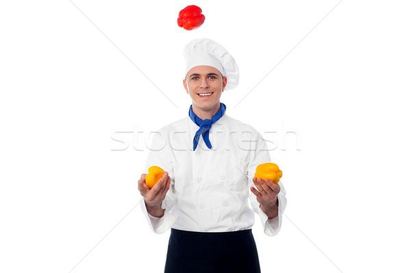 Wykwalifikowany kucharz żonglerka młodych papryka kolory Zdjęcia stock © stockyimages