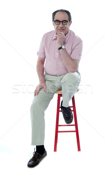 Confident senior man resting on stool Stock photo © stockyimages