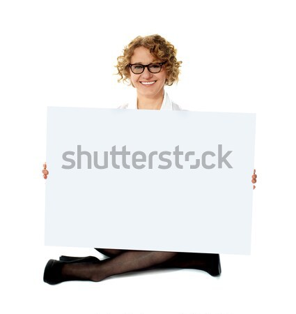 Female employee holding white blank banner ad Stock photo © stockyimages