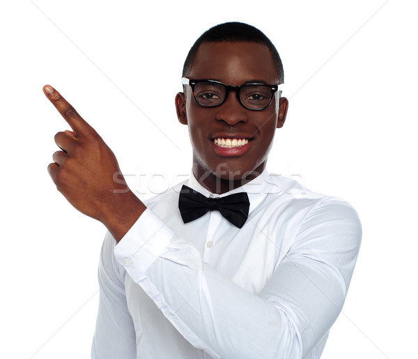 Welldressed young person pointing away Stock photo © stockyimages