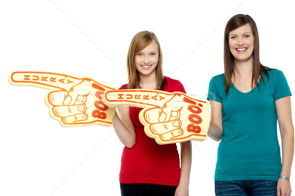 Cheerful fans pointing the big foam hand sideways Stock photo © stockyimages