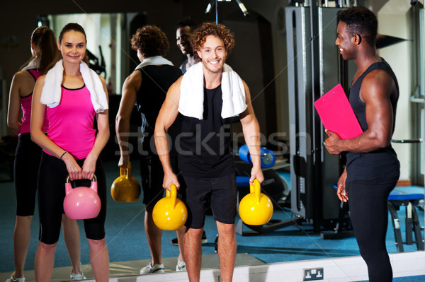 Happy man and woman lifting kettlebell Stock photo © stockyimages
