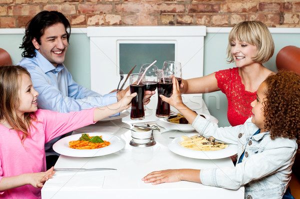 Family raising their glasses before eating Stock photo © stockyimages