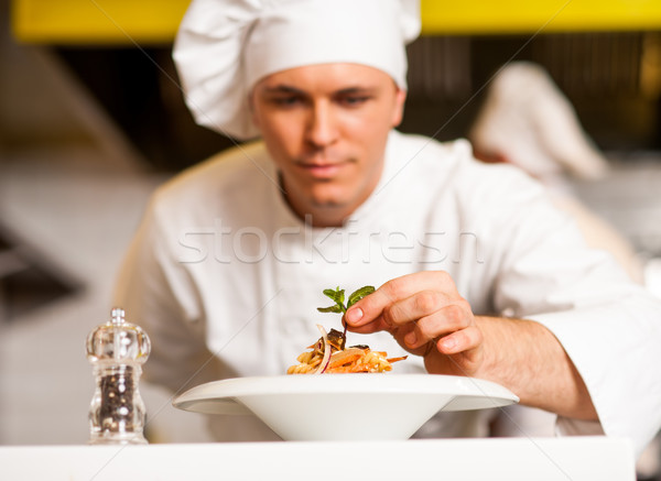 Chef decorating pasta salad with herbal leaves Stock photo © stockyimages