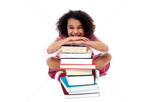 Aranyos iskolás lány dől boglya könyvek mosolyog Stock fotó © stockyimages