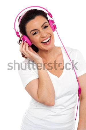 Attractive cheerful woman enjoying music Stock photo © stockyimages