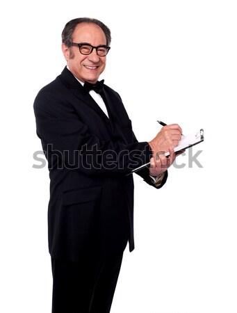 Bel homme écrit presse-papiers souriant regarder caméra Photo stock © stockyimages
