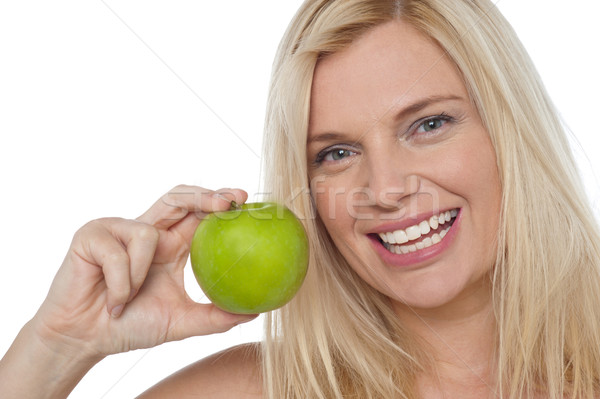 Closeup shot of a cheerful woman holding an apple Stock photo © stockyimages