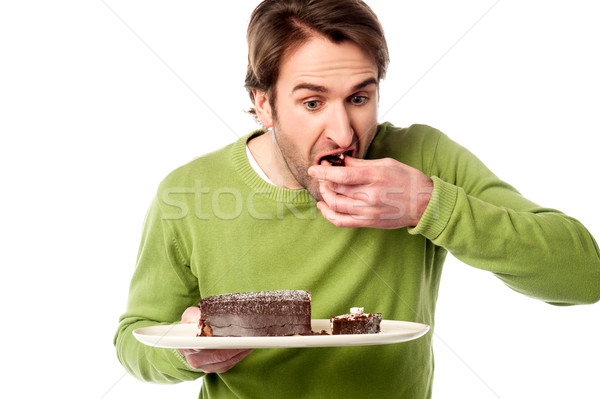 Young man tasting chocolate cake in hurry Stock photo © stockyimages