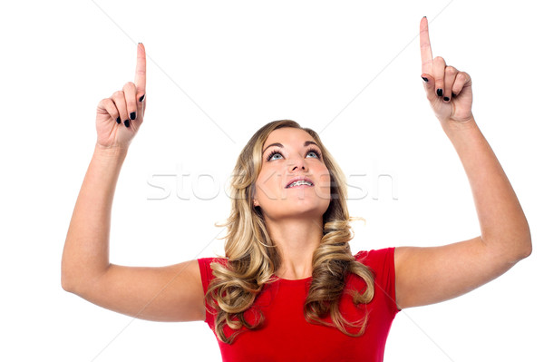 Teen girl looking and indicating upwards Stock photo © stockyimages
