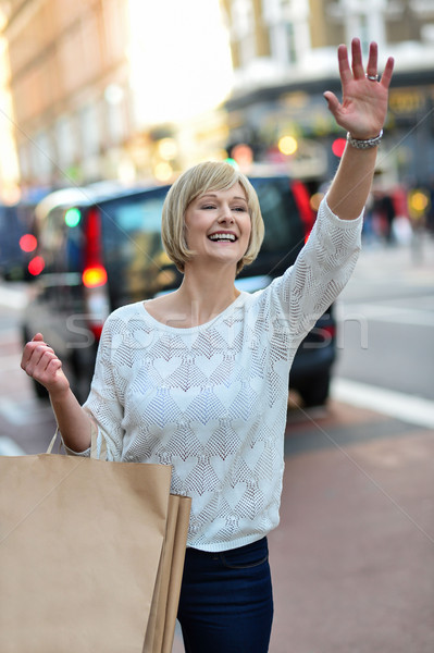 Casual woman hailing a taxi cab Stock photo © stockyimages