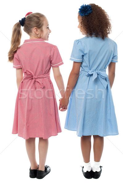 Vue arrière filles uniforme scolaire école mains tenant vue arrière Photo stock © stockyimages