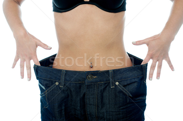 Woman shows her weight loss. Stock photo © stockyimages