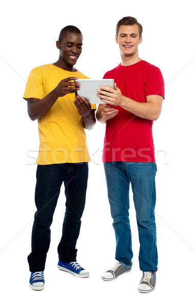 Full length shot of guys operating portable device Stock photo © stockyimages