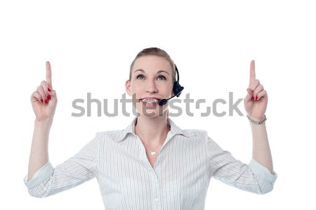Young call center woman pointing up Stock photo © stockyimages
