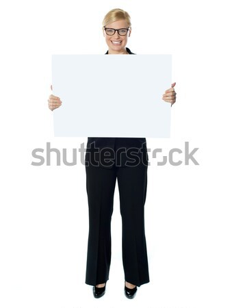 Smiling young lady holding blank banner ad Stock photo © stockyimages