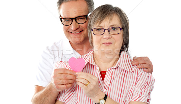 Matured smiling couple holding paper heart Stock photo © stockyimages
