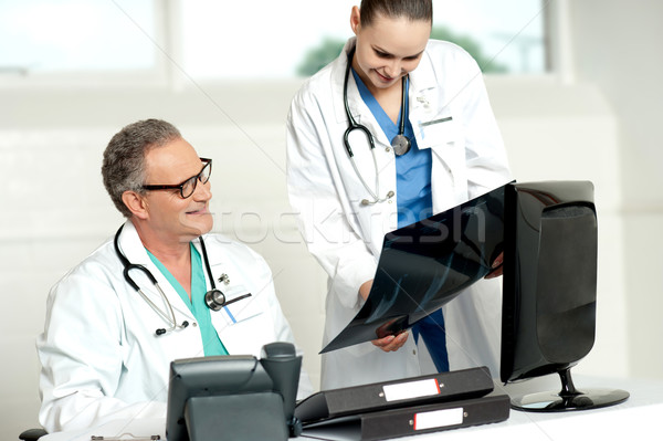 Team of two doctors reviewing x-ray report Stock photo © stockyimages