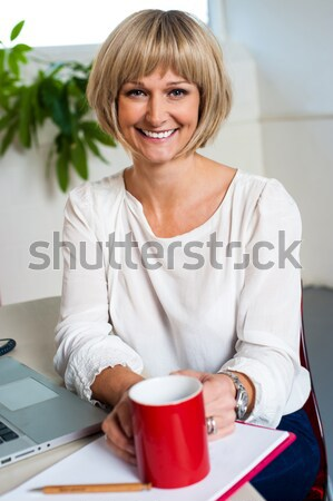Cheerful woman holding coffee mug and working Stock photo © stockyimages