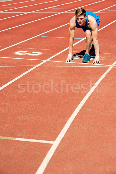 Athletic man on track, all set for race. Stock photo © stockyimages