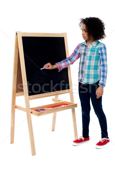Young school girl writing on blackboard Stock photo © stockyimages