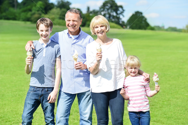 Cheerful family holding yummy ice cream cones Stock photo © stockyimages