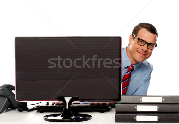 Man peeping from behind computer screen Stock photo © stockyimages