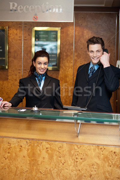 Male and female at hotel reception busy working Stock photo © stockyimages