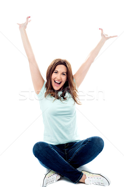 Woman with hands up sitting in crossed legs  Stock photo © stockyimages