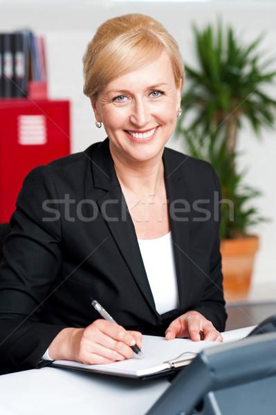 Female secretary writing on notepad Stock photo © stockyimages