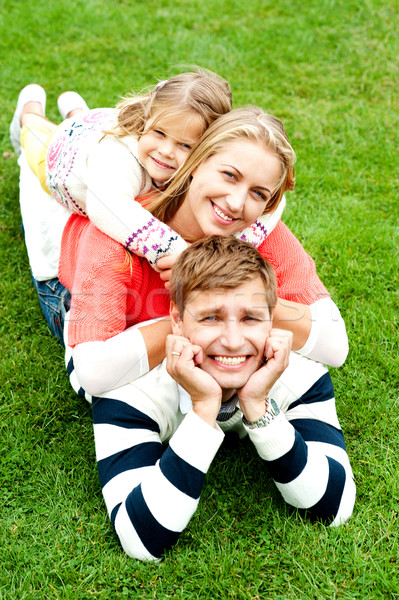 Husband, wife and child piled on each other Stock photo © stockyimages
