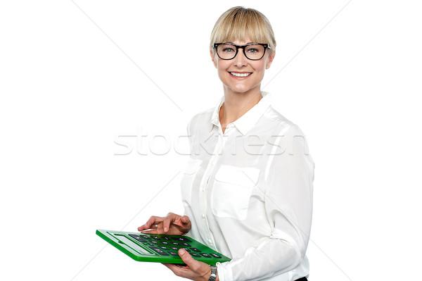 Secretary using large green calculator Stock photo © stockyimages