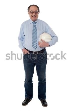 Senior architect holding hard-hat, full length Stock photo © stockyimages