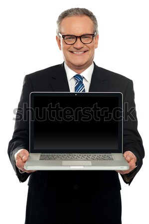 Senior executive standing with open laptop Stock photo © stockyimages
