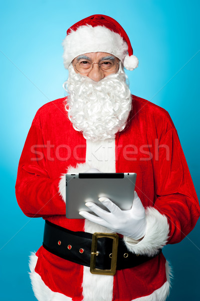 Modern Santa using digital touch screen device Stock photo © stockyimages