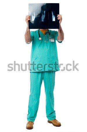 Doctor reviewing patient's x-ray report Stock photo © stockyimages