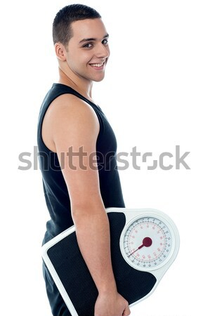 Fitness man with weighing scale Stock photo © stockyimages