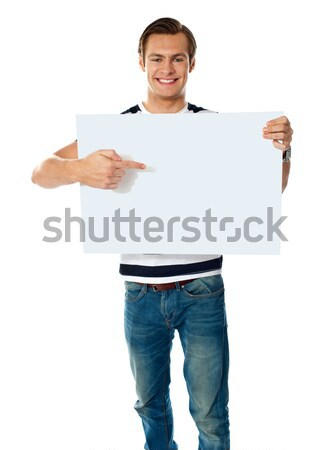 Portrait of young man pointing at blank signboard Stock photo © stockyimages