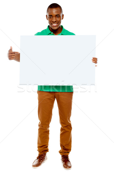 Casual young guy pointing towards placard Stock photo © stockyimages