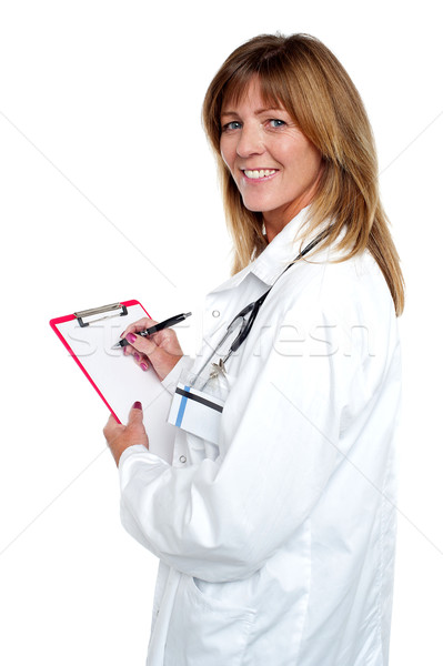 Beautiful smiling physician writing prescription Stock photo © stockyimages