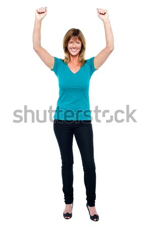 Excited woman in celebration mood with raised arms Stock photo © stockyimages
