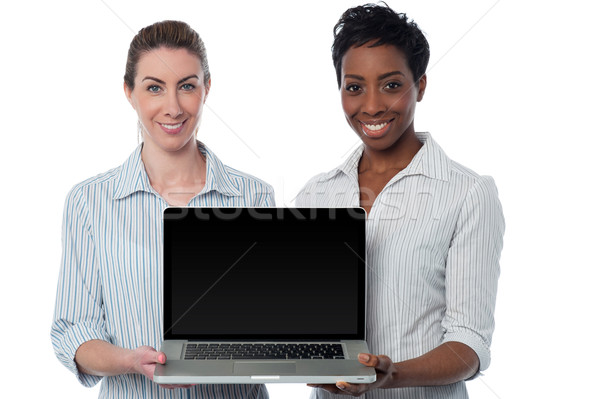 Saleswomen presenting brand new laptop Stock photo © stockyimages