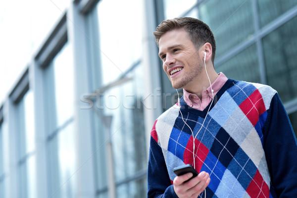 Gündelik adam müzik dışında modern bina yakışıklı Stok fotoğraf © stockyimages
