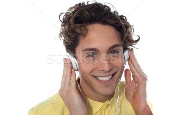 Toevallig jonge man luisteren muziek hoofdtelefoon geïsoleerd Stockfoto © stockyimages