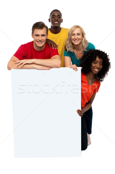Stock photo: Group of teenagers displaying white banner