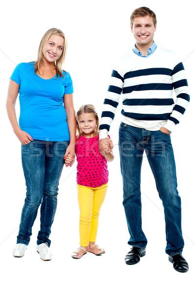 Sweet little kid standing in between her parents Stock photo © stockyimages