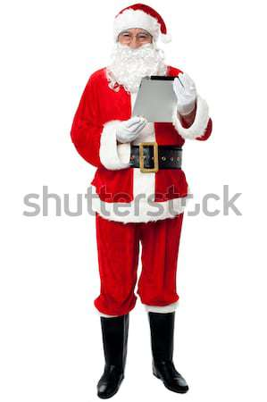 Father Christmas using new tablet device Stock photo © stockyimages