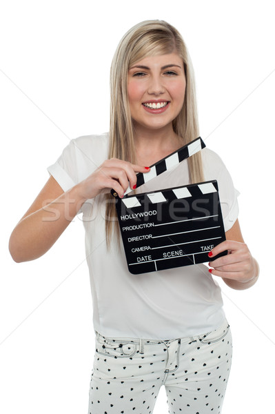 Cheerful teen girl with clapboard in hand Stock photo © stockyimages