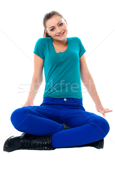 Cute girl sitting casually on the studio floor Stock photo © stockyimages